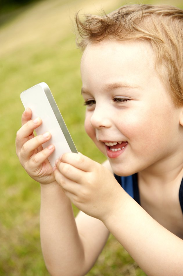 Boy holding white cell phone in park, smiling