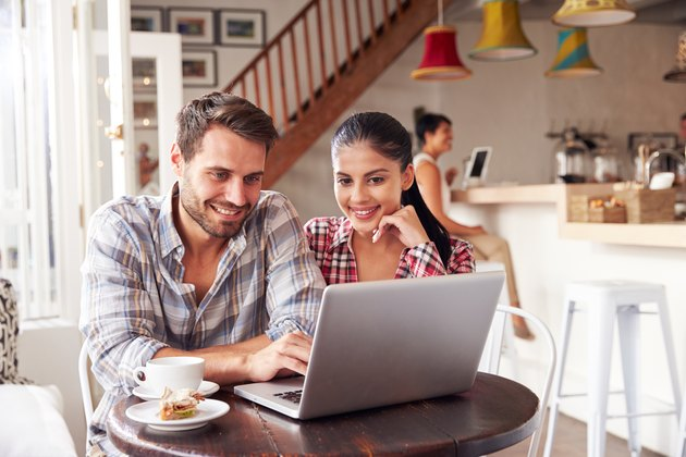 Young couple using laptop in a cafe smiling