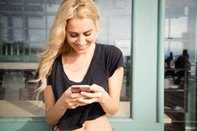 Pretty young woman sends a text message from her phone.