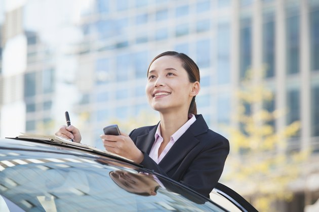 Businesswoman Standing by Car Using Phone and Taking Notes