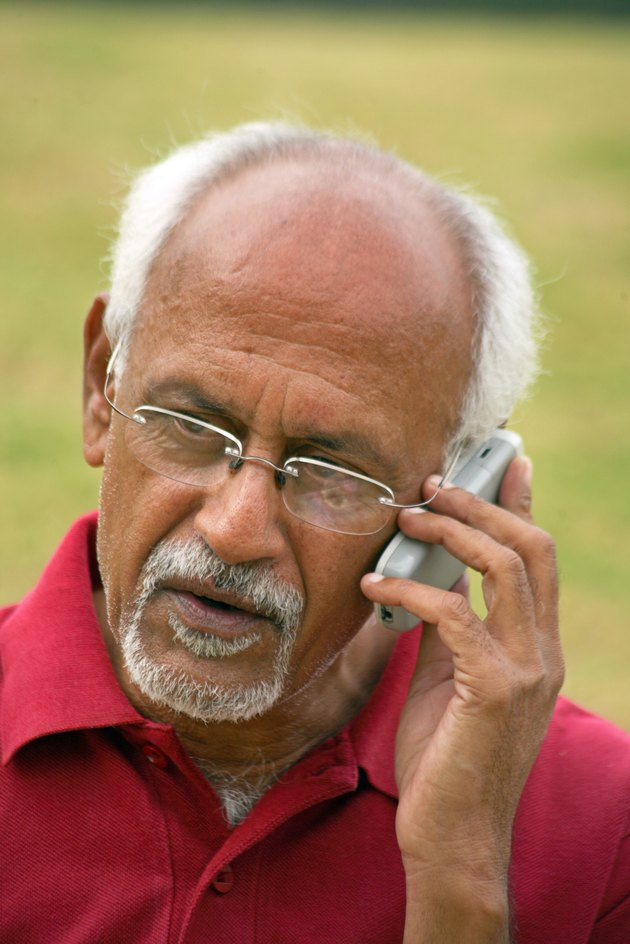 An old man talking on a cell phone