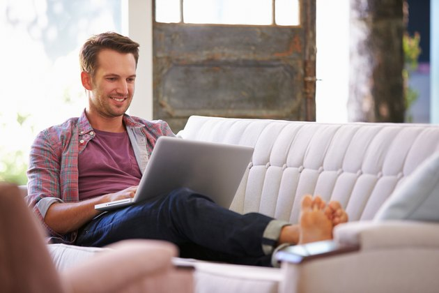 Man Relaxing On Sofa At Home Using Laptop Computer