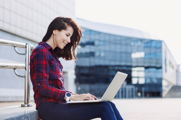 Student girl using laptop outdoors