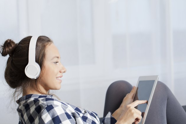 Woman With Headphones Listens Music On Tablet PC