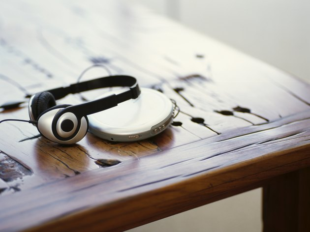 headphones and a personal stereo on a wooden table