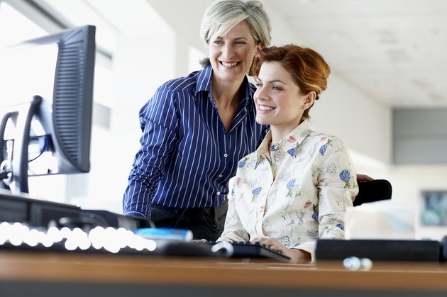 Two businesswomen looking at monitor in office, smiling