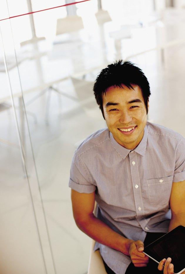Portrait of smiling businessman using digital tablet in office