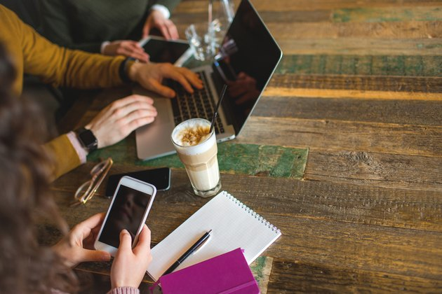 Hands over laptop smartphone tablet with coffee in trendy cafe