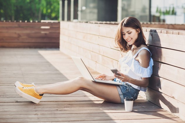 Young trendy girl using a laptop outdoors