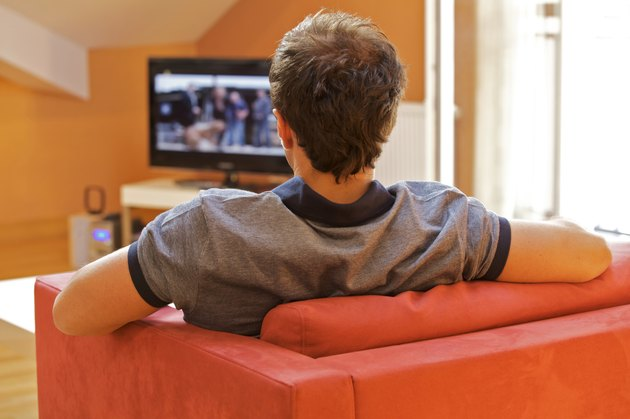 Rear view of a young man watching tv on a red chair
