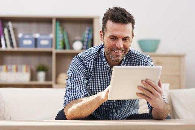 Smiling handsome man using digital tablet at home