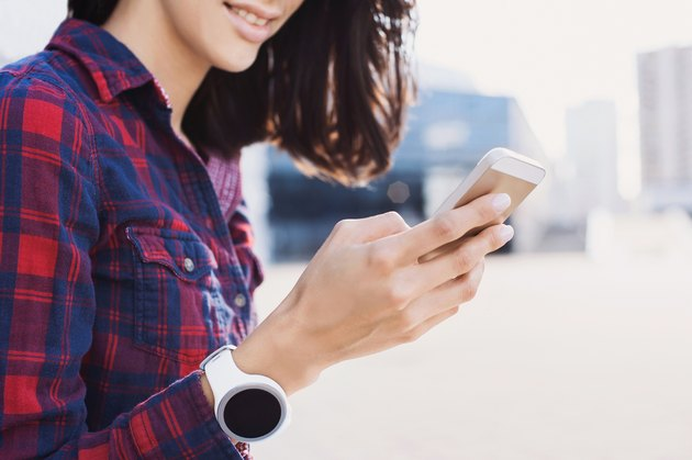Girl wearing smartwatch using smart phone