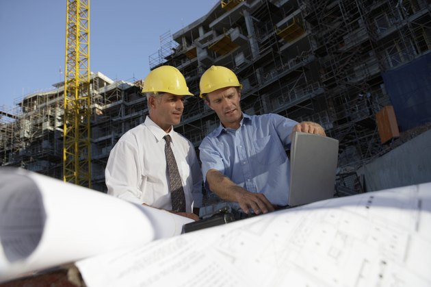 Two Men Wearing Hard Hats Looking Down at a Laptop Computer on a Building Site
