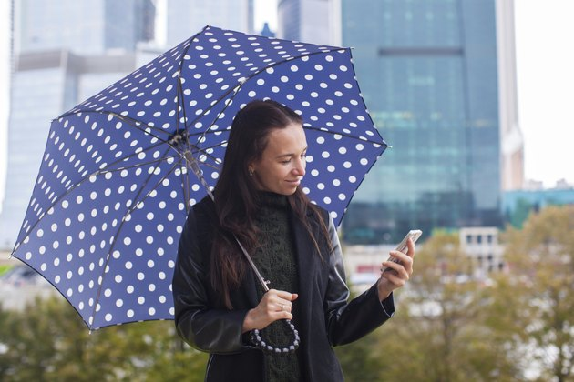 Young woman talking on the phone with umbrella in hand