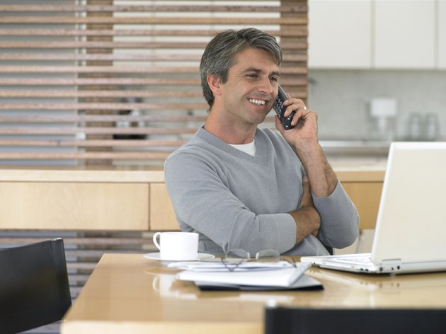 Man sitting at kitchen table using laptop and mobile phone, smiling