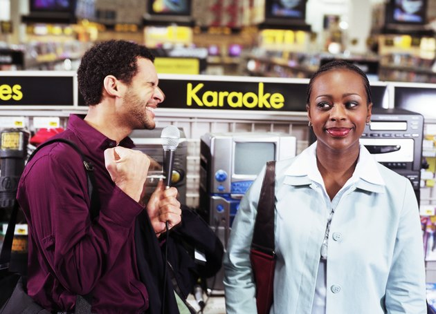 Young Couple Shopping in an Electronics Store, Man Performing Karaoke