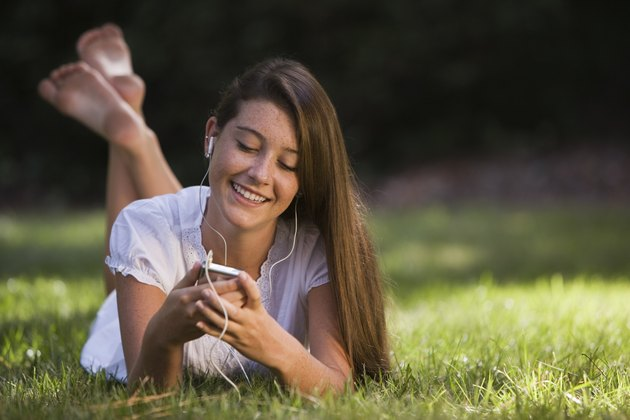 Smiling teenage girl listening to music