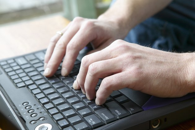 Man typing on laptop keyboard
