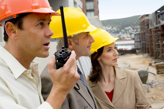 Foreman with architects at construction site