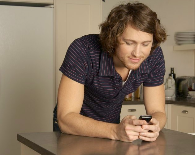 Young man text messaging in kitchen