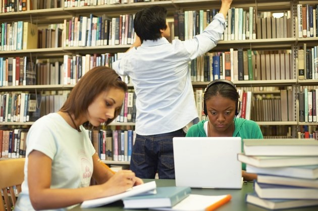 Two female students studying in library, male student in background