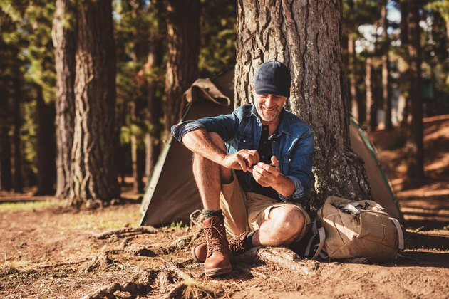 Senior man sitting at campsite