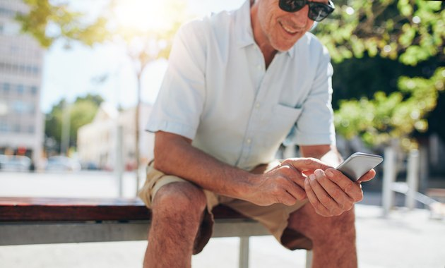 Mature man sitting outdoors using mobile phone