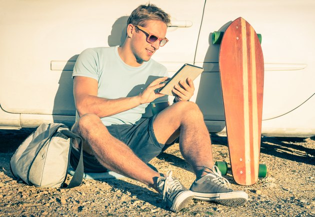 Young hipster man with tablet sitting next his car