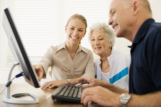 Woman helping couple use computer
