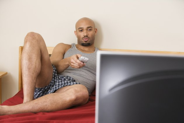African man watching television in bed