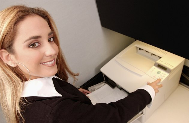 Young blonde female is office worker at fax machine