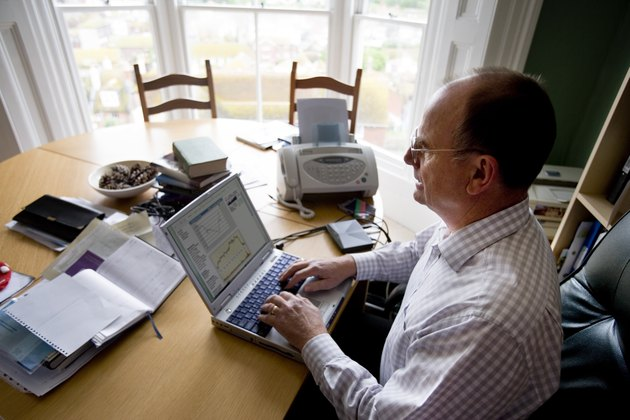 Man working on laptop at dining room table