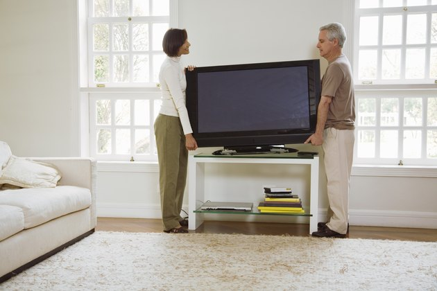 Couple moving flat screen television