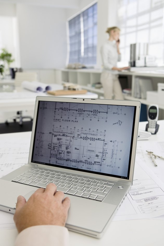 Blueprints on computer screen with businesswoman talking on cell phone