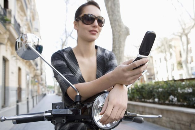 Woman on moped with cell phone