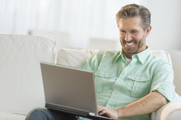 Happy Man Using Laptop On Sofa