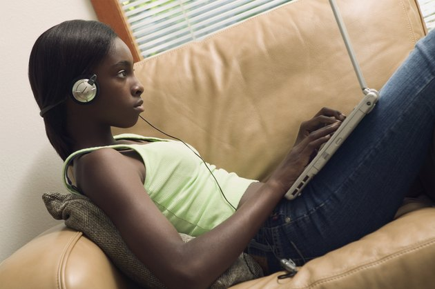 Side profile of a teenage girl operating a laptop