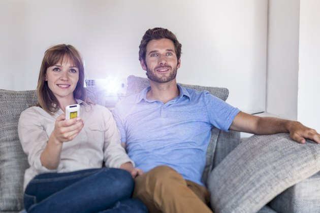 Couple watching a movie with a video projector on sofa