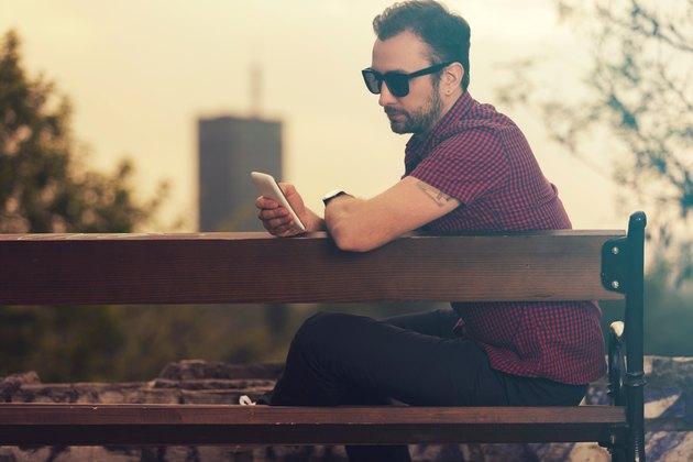 Modern guy using cellphone outdoors.