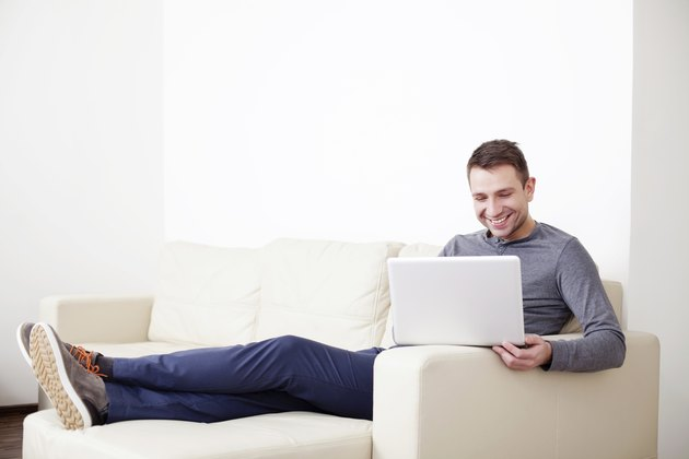 Man sitting on sofa with digital tablet