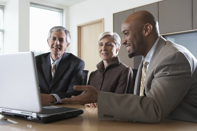 Three executives using laptop during meeting in boardroom, smiling