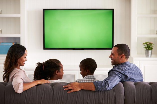 Parents and children watching TV, looking at each other