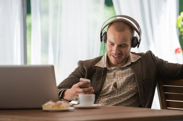 Young man listening to music with headphones at a cafe