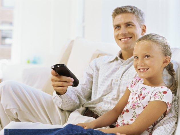 father sitting with his daughter holding a remote control
