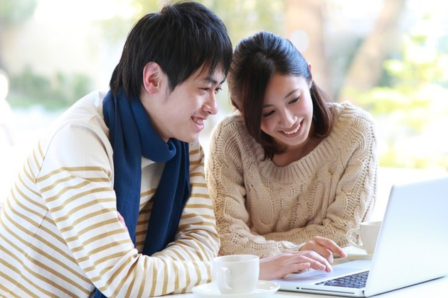 Man and woman sat smiling at laptop with cup and saucer