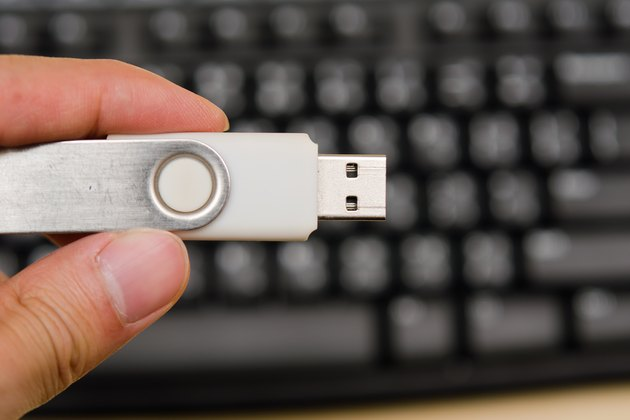 USB thumb drive with hand holding on keyboard background