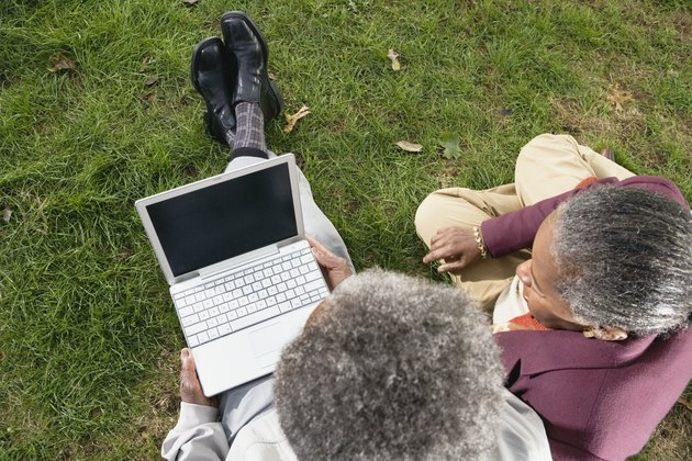 Senior African couple using laptop on grass outdoors