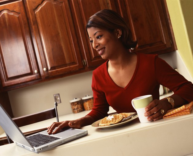 Woman using laptop and eating