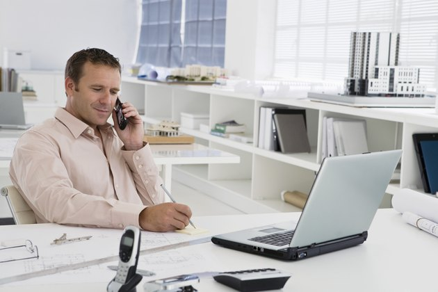 Businessman using laptop while on cell phone