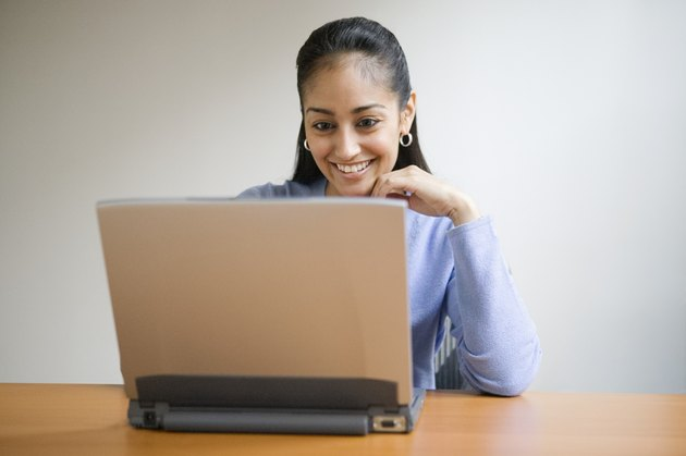Young adult smiling with computer